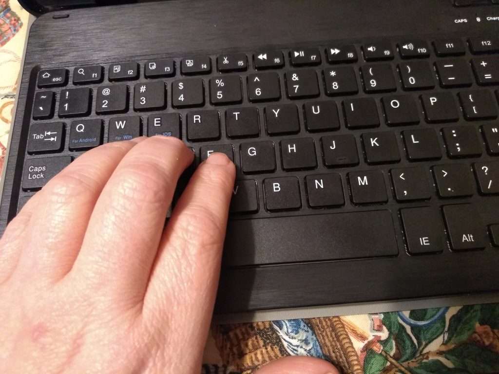 Hand on a keyboard preparing to search for favorite crochet YouTube channels