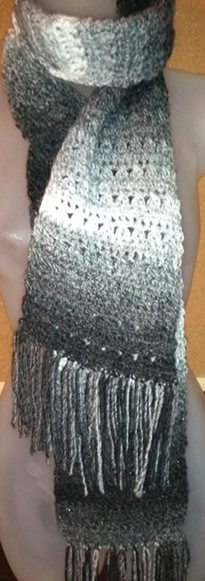 Gray and white and black scarf with fringe. The twisted Stitches Cowl Fringed Scarf display.