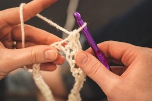 person holding purple crochet hook and white yarn; one way of using crochet as meditation