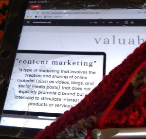 An iPad screen showing a slide from a video conference. On top of the screen is a work-in-progress of red yarn with a silver crochet hook visible at the bottom. An example of what not to do if you want to be crocheting without distractions.