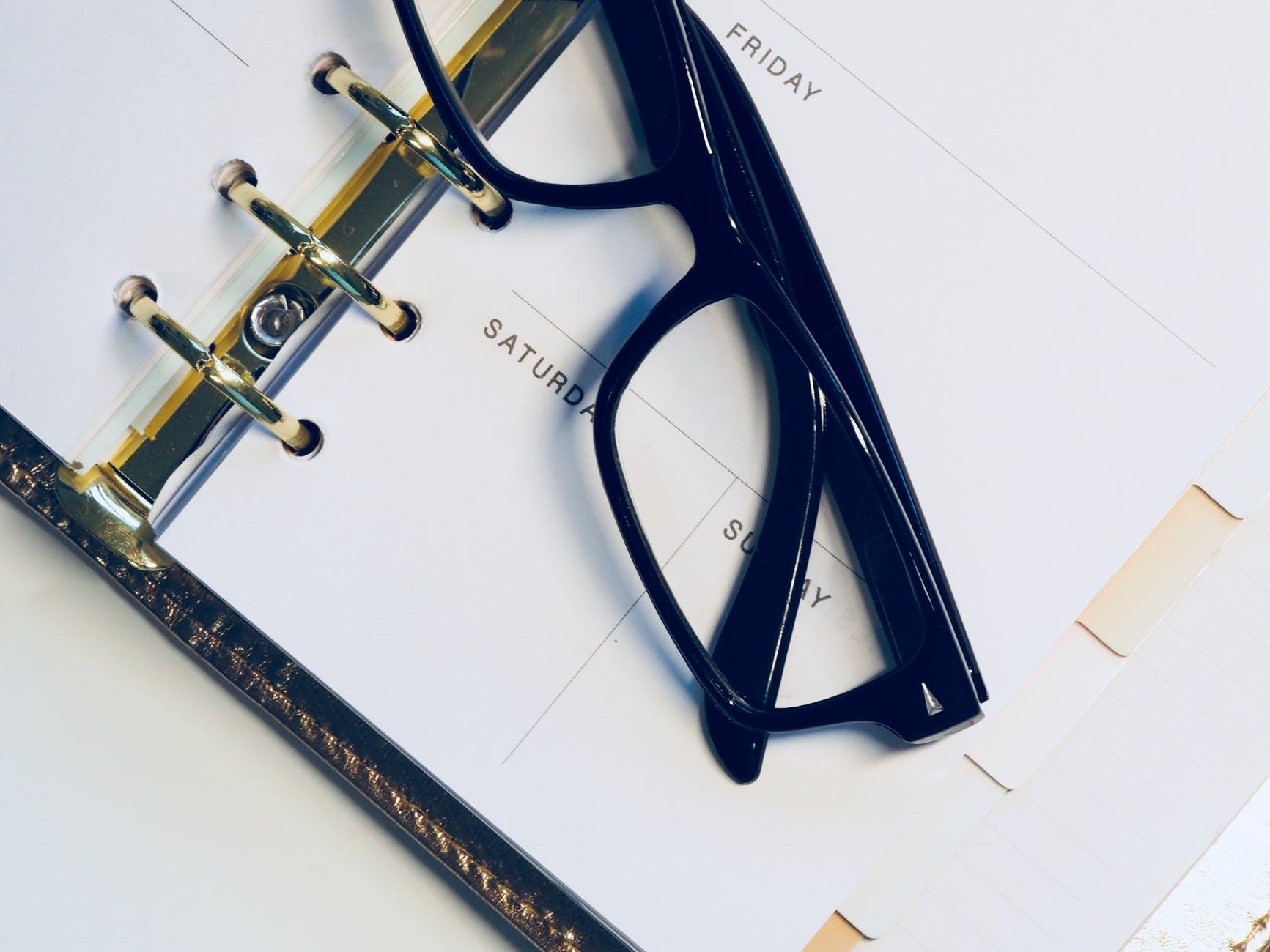 black framed wayfarer style eyeglasses on white surface that looks like a calendar for planning what's next